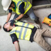 Injured worker being properly attended to at site of workplace accident