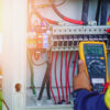 Electrician performing work on open electrical panel