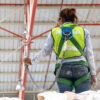 Warehouse worker verifying integrity of safety harness